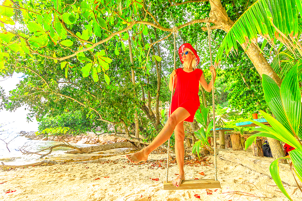 Summer vacation concept. Happy lifestyle tourist woman in red dress swinging on tropical beach under coconut palm trees of Anse Severe, La Digue, Seychelles, Indian Ocean.