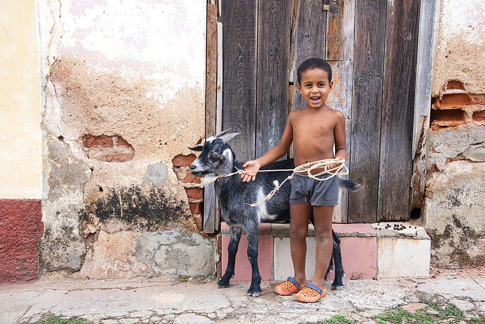 Local boy with his goat on a city street in Trinidad, Cuba, West Indies, Caribbean, Central America