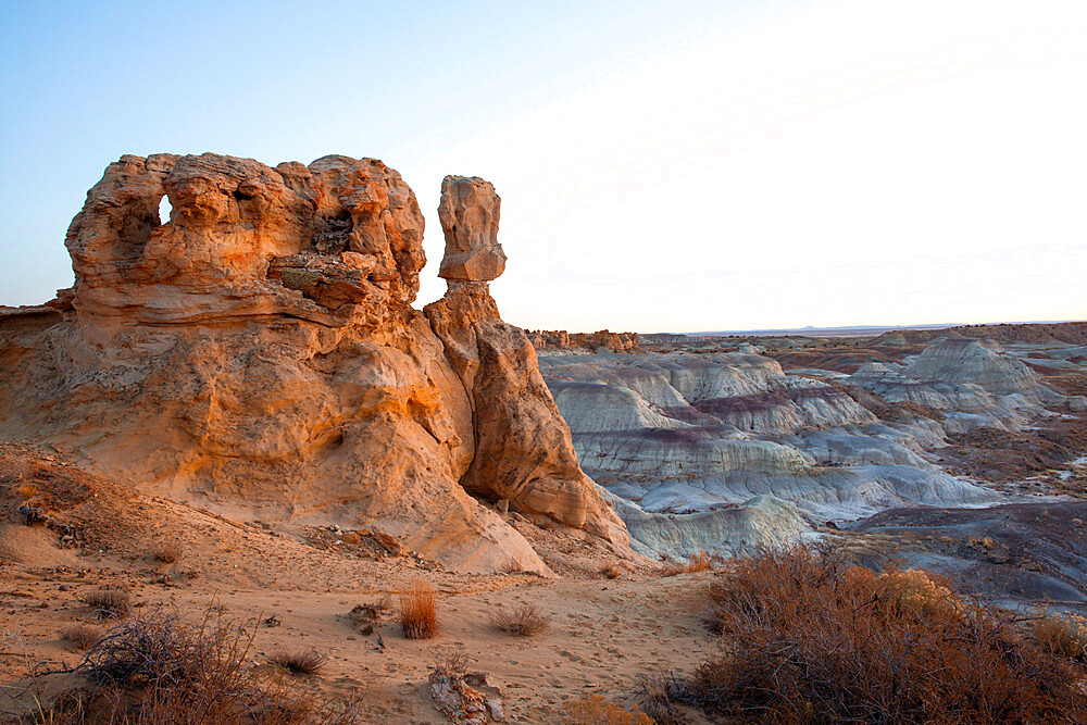 Sandstone sculptures in Bisti/De-Na-Zin Wilderness in New Mexico at dusk.