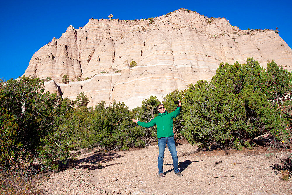 Man posing for a selfie in front of Kasha-Katuwe Tent Rocks National Monument, New Mexico. Model release 243