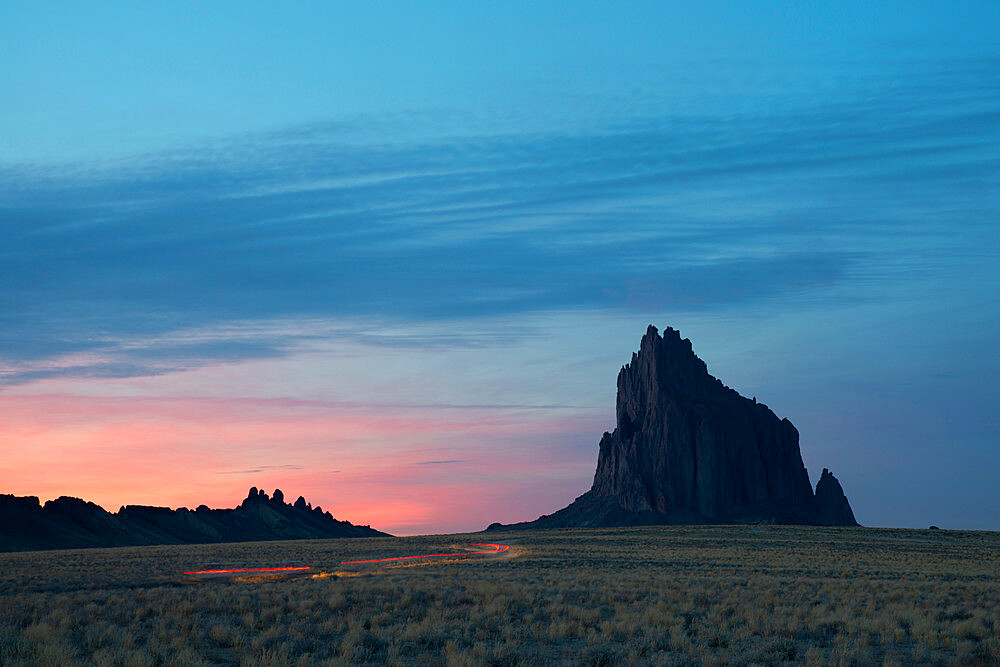 Light trails leading to Shiprock in Farmington, New Mexico, at dusk.