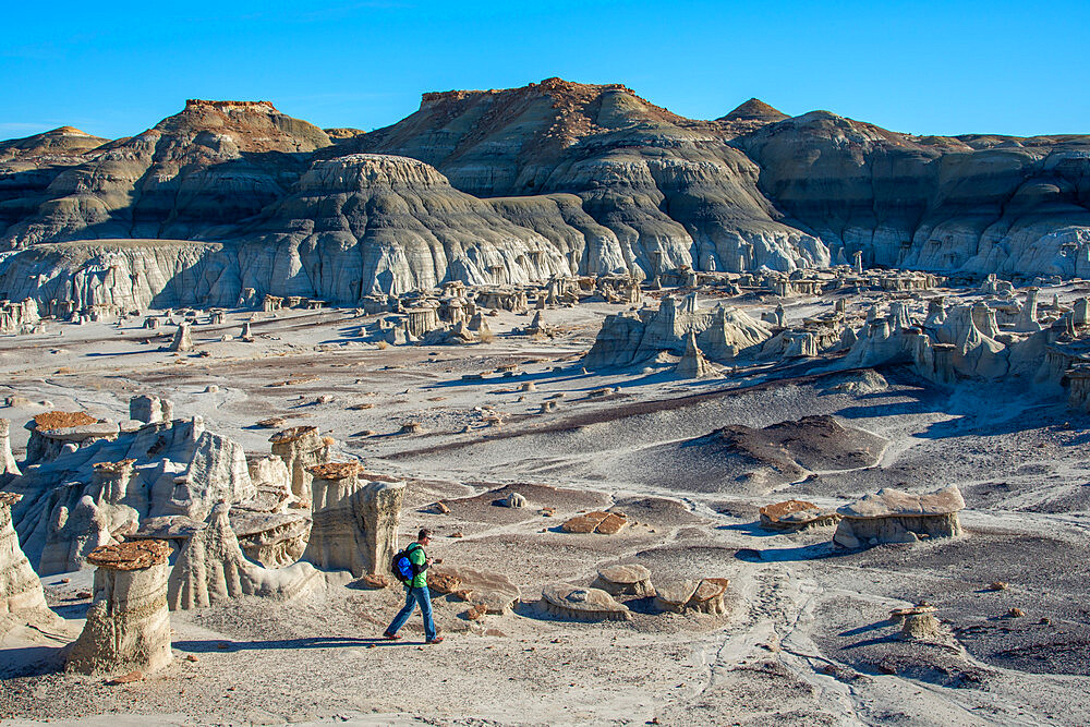 Hiking around hoodoo sandstone formations in Bisti/De-Na-Zin Wilderness, New Mexico.
