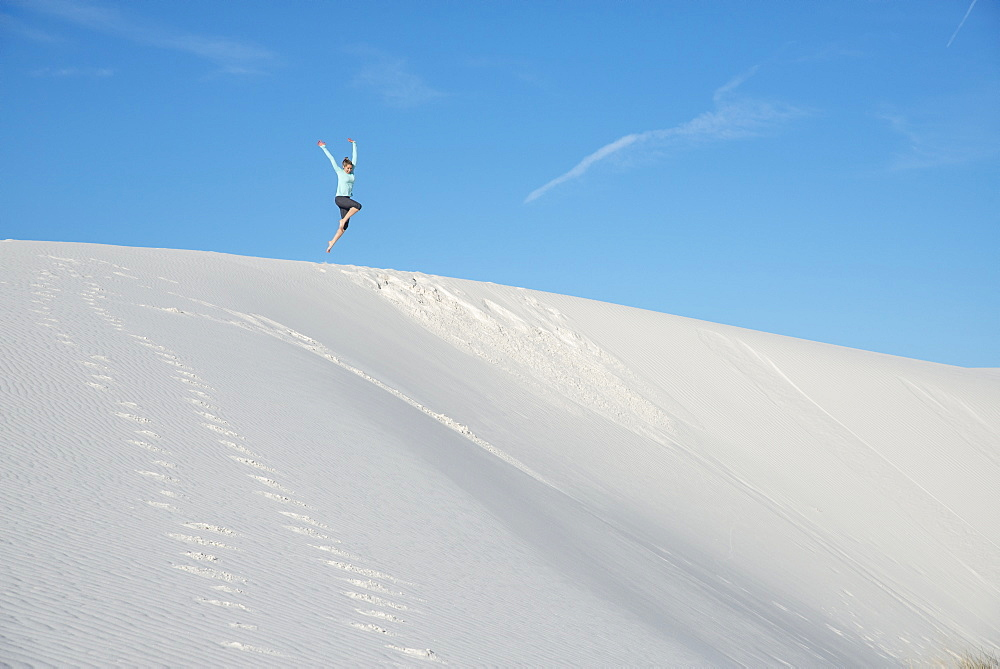 Jumping off a sand dune in White Sands National Park, New Mexico, United States of America, North America