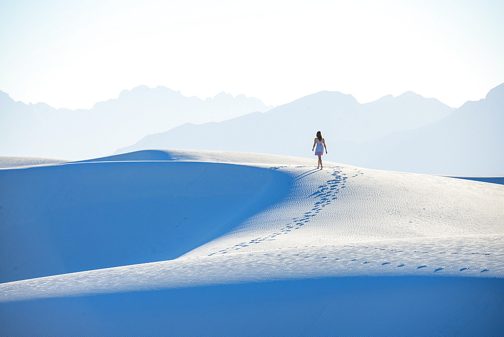 A woman walking along a dune's ridge in White Sands National Park, New Mexico, United States of America, North America