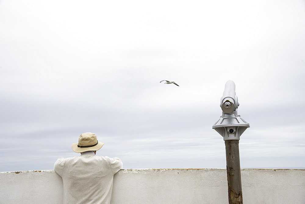 Man peering over a wall beside a telescope along the Algarve coast of southern Portugal. - 1315-2