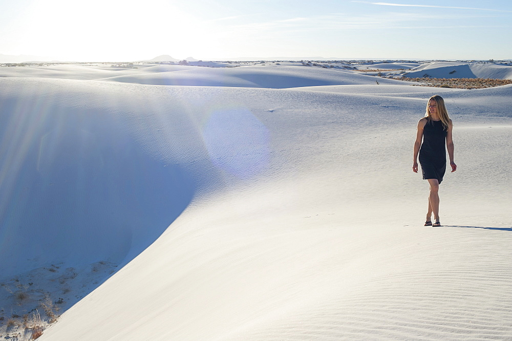 A woman strolls along the ridge of a pure white sand dune in White Sands National Park, New Mexico, United States of America, North America
