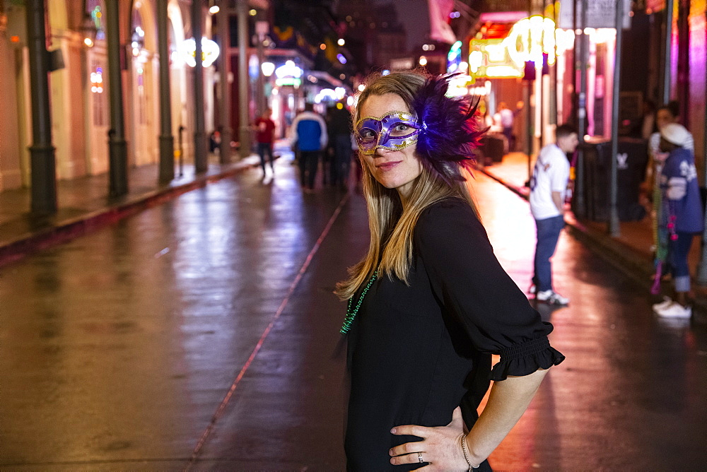 Woman ready to celebrate Mardis Gras on Bourbon Street in the French Quarter of New Orleans.
