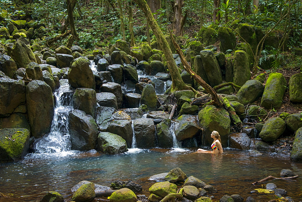 Woman lounging in a pool beneath a waterfall in Kauai, Hawaii, United States of America, North America