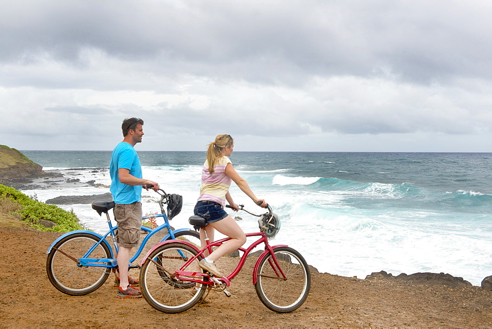 Couple on bikes looking out at the ocean on the shores of Kauai, near Kapaa, Kauai, Hawaii, United States of America, North America