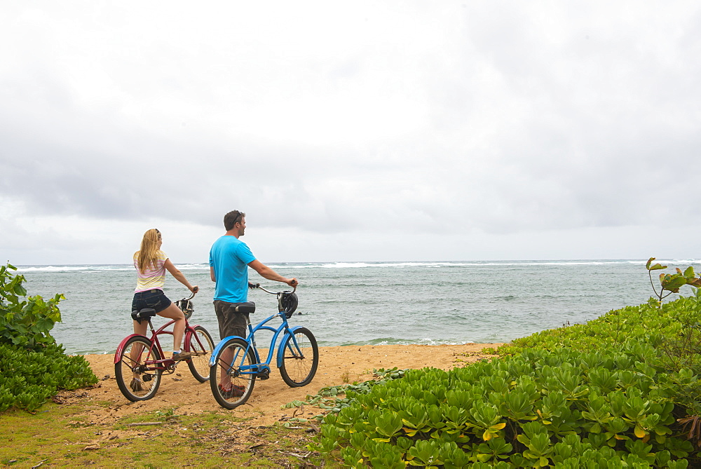 Couple with bicycles looking out at the ocean on Kauai near Kapaa, Hawaii, United States of America, North America