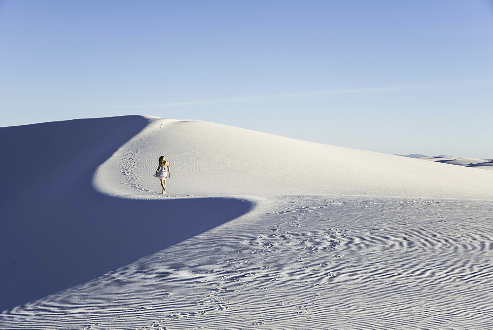 Woman walking along a white sand dune, cast in blue late-afternoon light, in White Sands National Monument, New Mexico, United States of America, North America