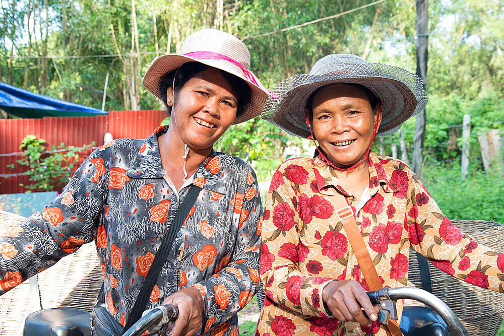 Two local women with their bicycles smiling together in Siem Reap, Cambodia, Indochina, Southeast Asia, Asia - 1315-310