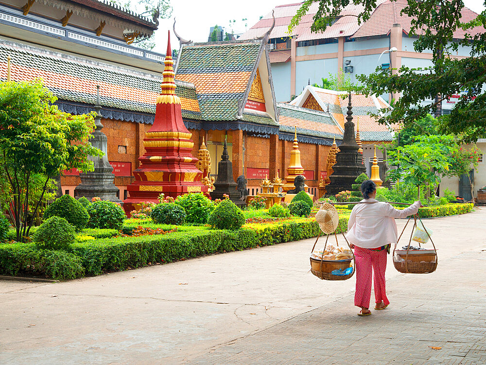 Woman carrying baskets over her shoulders outside a temple in Siem Reap, Cambodia