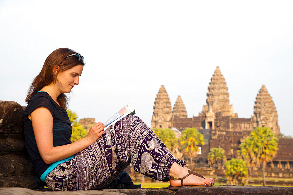 Female tourist reading a guidebook at Angkor Wat, a UNESCO world heritage site, in Siem Reap, Cambodia
