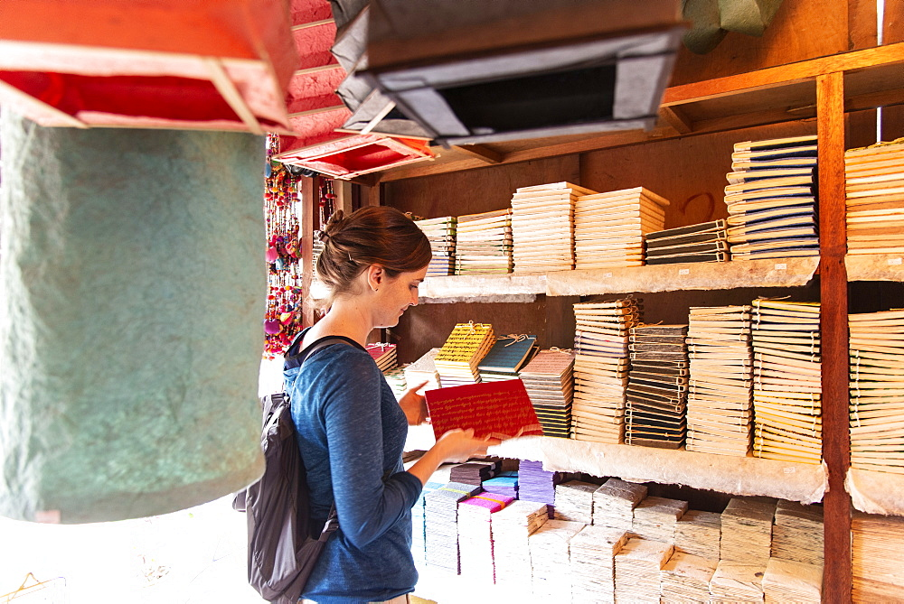 A tourist browses notebooks at a paper shop in Luang Prabang.