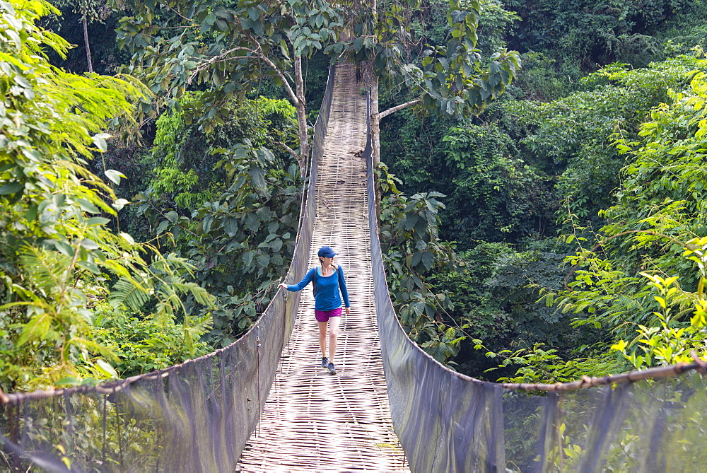 A woman crosses a precarious looking suspension bridge over the jungle in Laos.