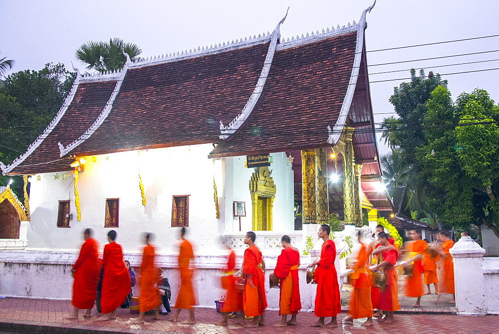 Buddhist monks receive rice from locals during an early morning daily ritual known as Sai Bat (morning alms) in Luang Prabang. - 1315-340