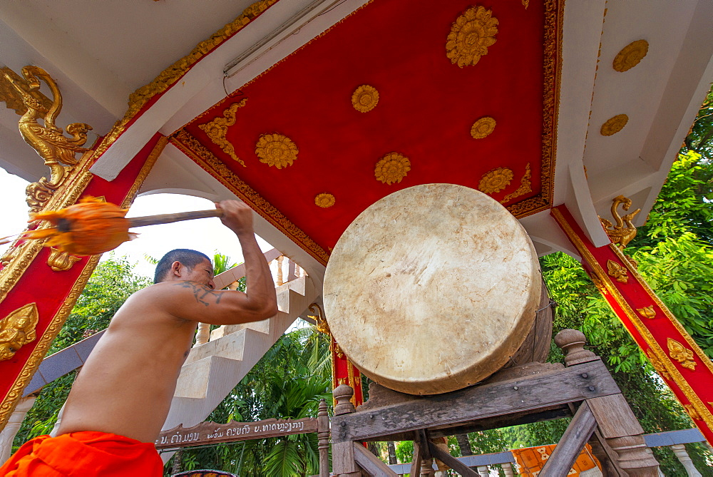A monk sounding a gong in Vientiane, Laos.