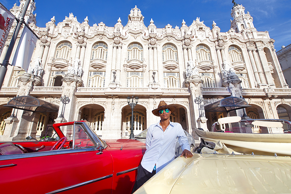 Taxi driver next to his vintage car in front of the Gran Teatro de La Habana, Havana, Cuba. Model released.