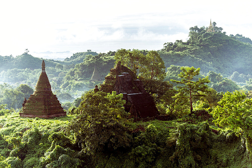The view from Shin Mra War Pagoda, showing small stupas on small jungle covered hills with mountain ridges in the background, Mrauk U, Rakhine, Myanmar (Burma), Asia