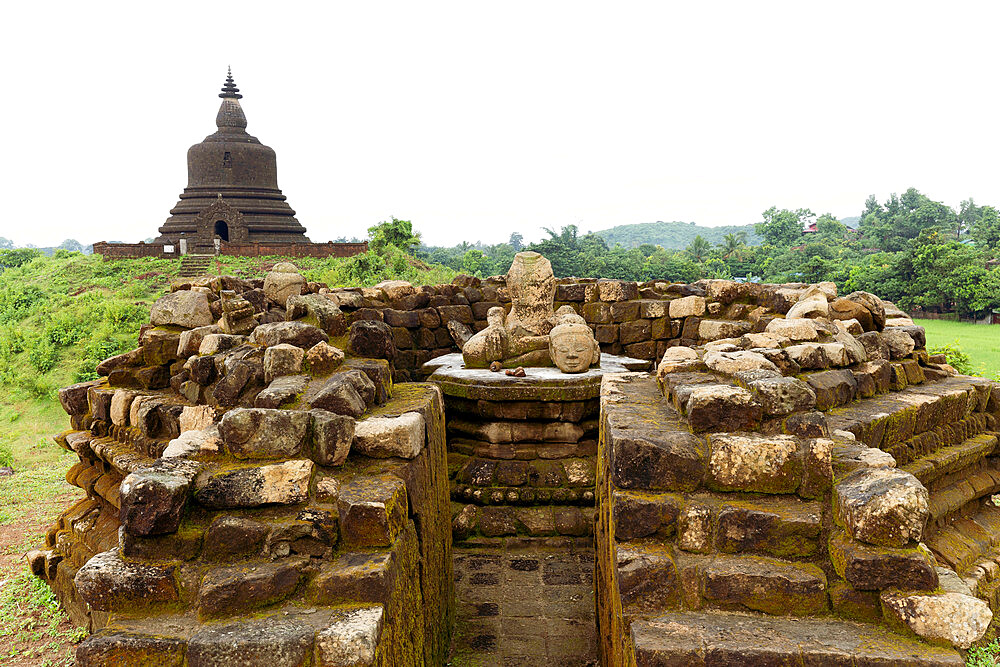 A ruined stone stupa with damaged Buddha statue in the centre, with West Myatazaung Pagoda in the background
