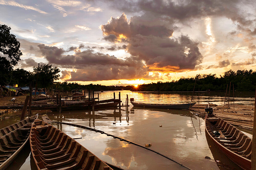Mrauk U boat jetty at sunset showing waterlogged canoes in the foreground, Mrauk U, Rakhine, Myanmar (Burma), Asia