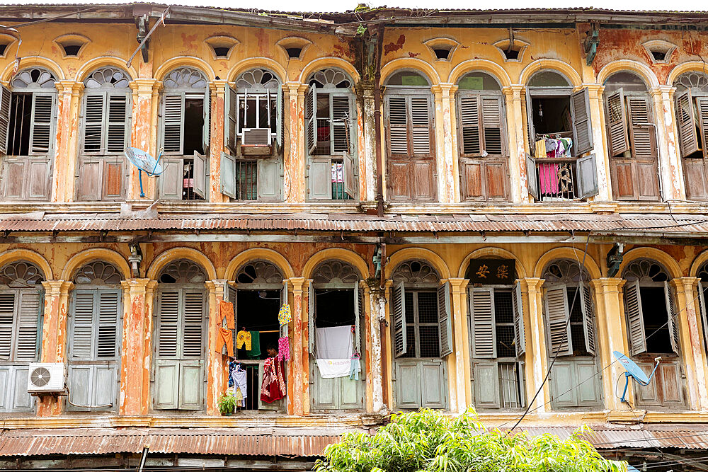 The first and second floors of an old colonial apartment building in Chinatown, showing archways and wooden doors, Yangon (Rangoon), Myanmar (Burma), Asia - 1317-29