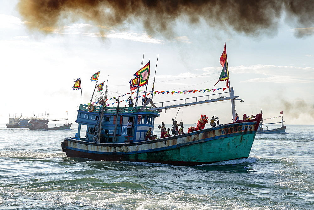 A fishing trawler at sea, taking part in the annual whale festival, with a lion dance on deck and other boats in the background, Vietnam, Indochina, Southeast Asia, Asia