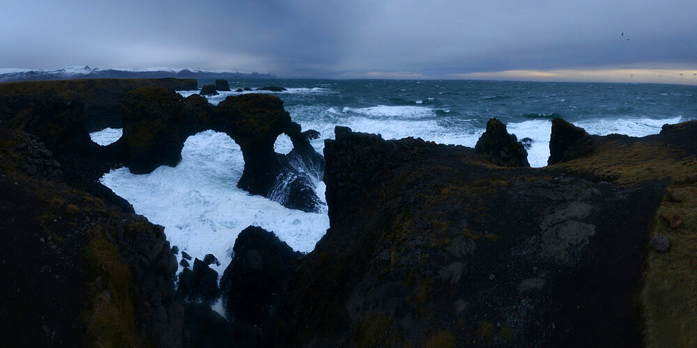 Waves crashing into lava cliffs and sea arch, Iceland, Polar Regions