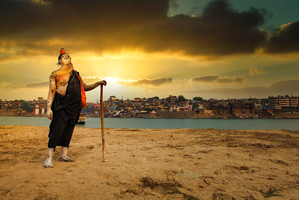 An Indian Hindu Sadhu (saint) on the banks of holy river of Ganges and Varanasi city in the background