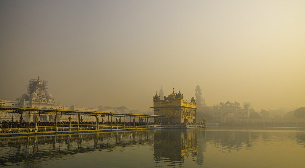 The Golden Temple at sunrise through fog. Amritsar, India - 1320-26