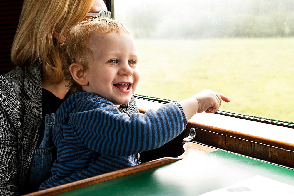 2 year old boy and Mother on old steam train carriage pointing out of window, Bluebell Railway, Sussex, UK