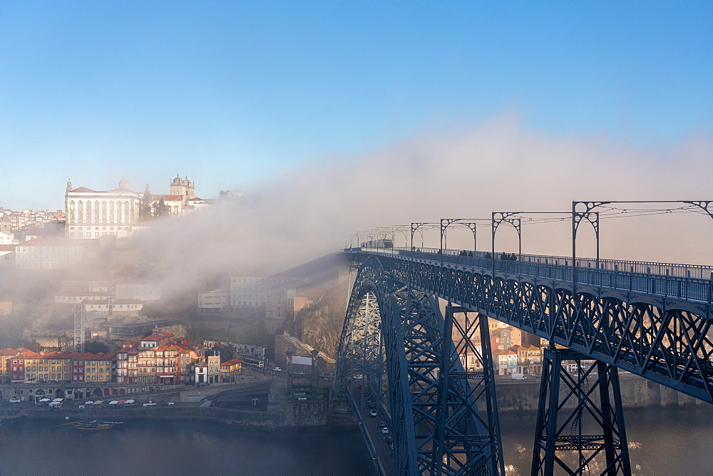 Dom Luís I Bridge with tram and view of Porto in the early morning mist