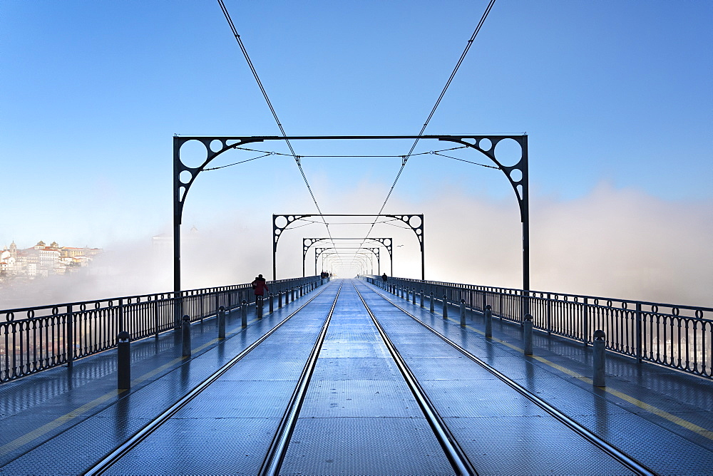 Tram tracks in the early morning mist running over Dom Luís I Bridge in Porto.