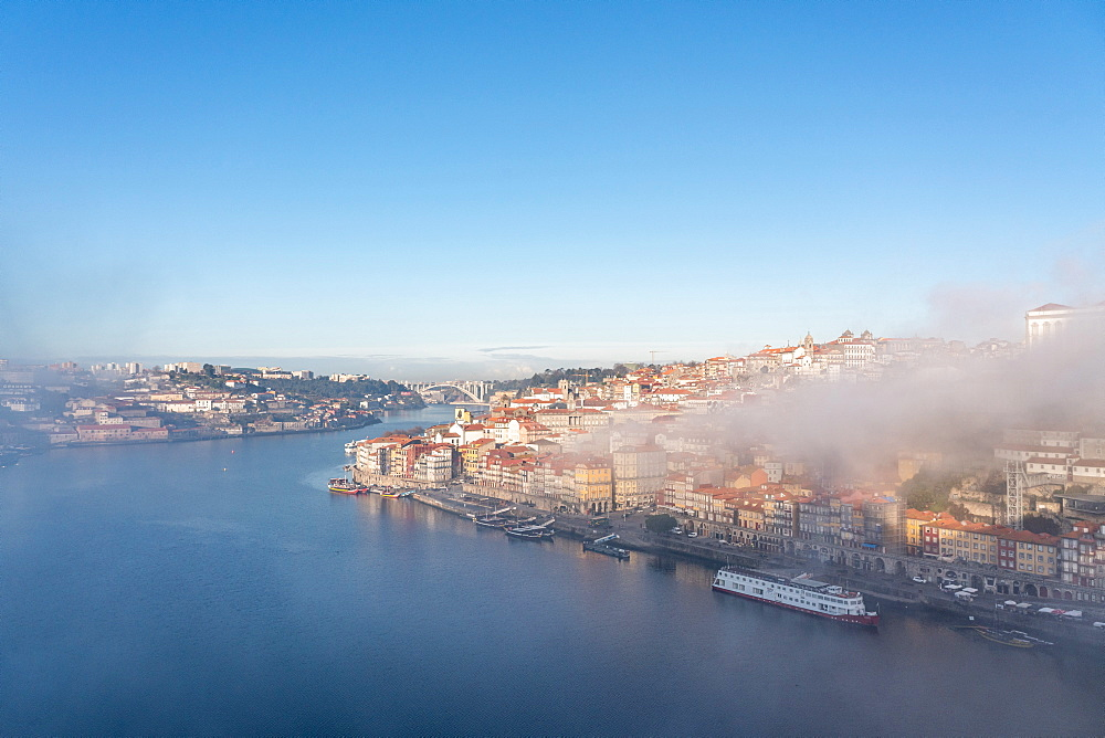 View of Porto in the early morning mist from Dom Luís I Bridge looking down to the river Douro, Portugal.