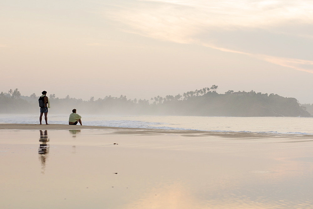 Two men watching the sunrise on Talalla beach, Sri Lanka, Asia