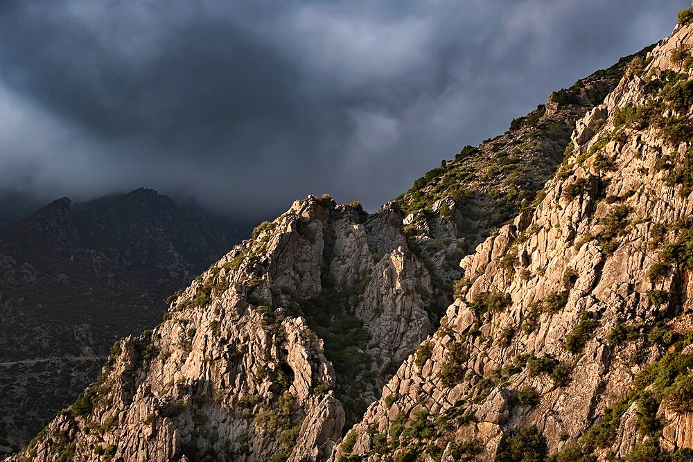 Sunset light on a rocky mountain and dark clouds in the sky, Chefchaouen, Morocco - 1336-185