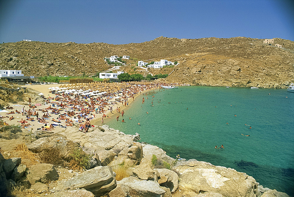 Tourists on the Super Paradise beach with small houses in the background, on Mykonos, Cyclades Islands, Greek Islands, Greece, Europe