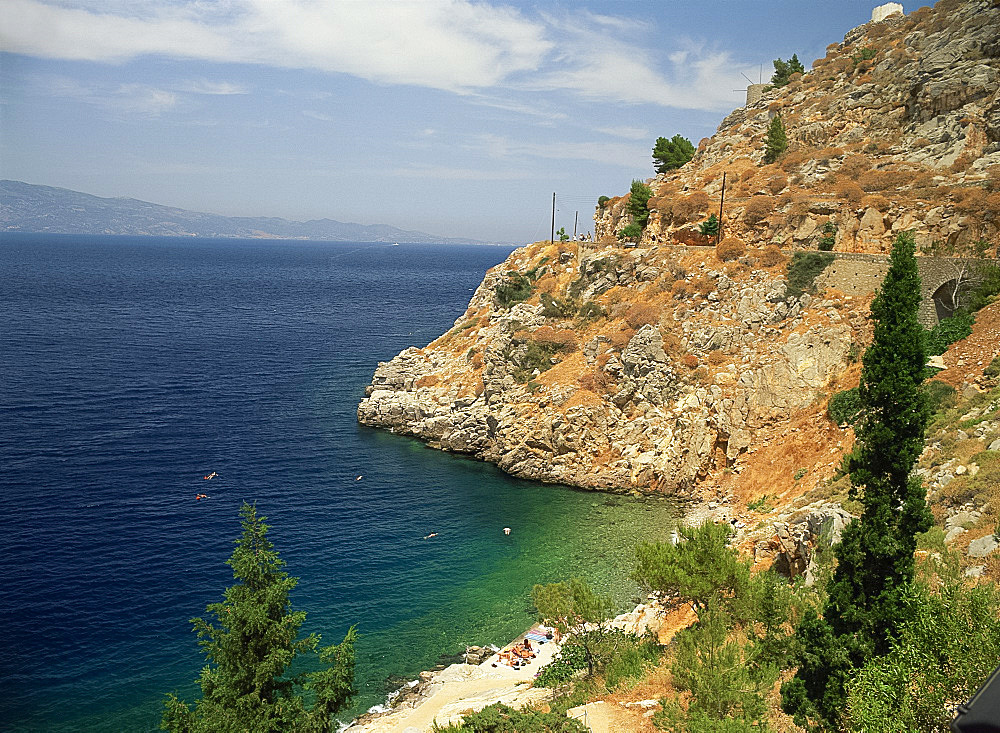 Swimmers in sea below cliffs on Hydra, Argo Saronic Islands, Greek Islands, Greece, Europe