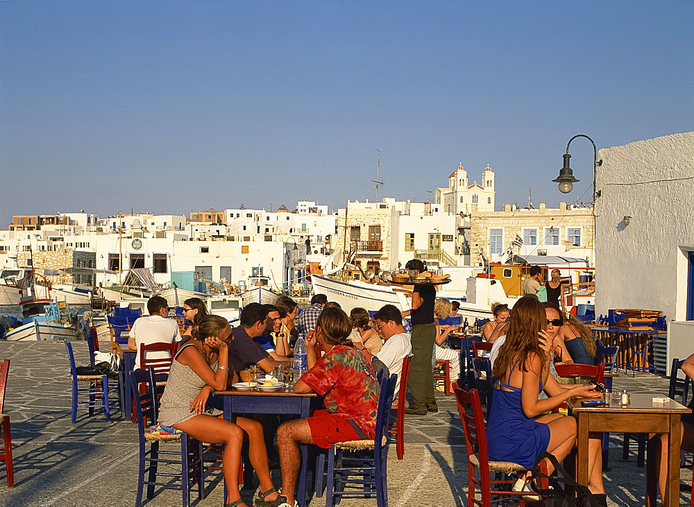 Tourists eating and drinking outside at a taverna in the town of Naousa on Paros, Cyclades, Greek Islands, Greece, Europe