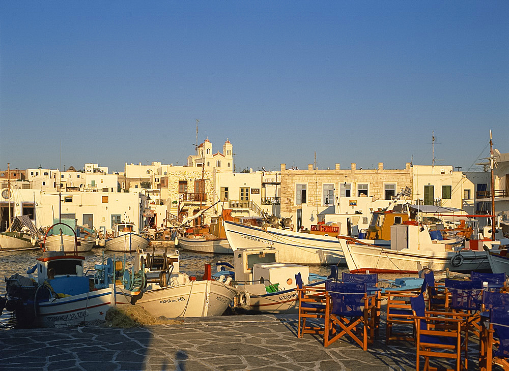 Tables and chairs on quayside, with boats in harbour in the town of Naousa on Paros, Cyclades, Greek Islands, Greece, Europe