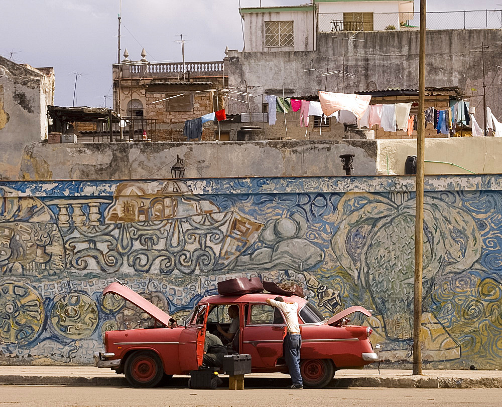 Two men repairing an old car parked in front of a colourful wall mural in central Havana, Cuba, West Indies, Central America