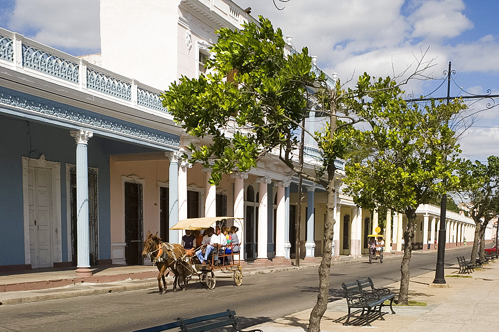 A horse and carriage going past row of columns in the Paseo del Prado, the main avenue, Cienfuegos, Cuba, West Indies, Central America