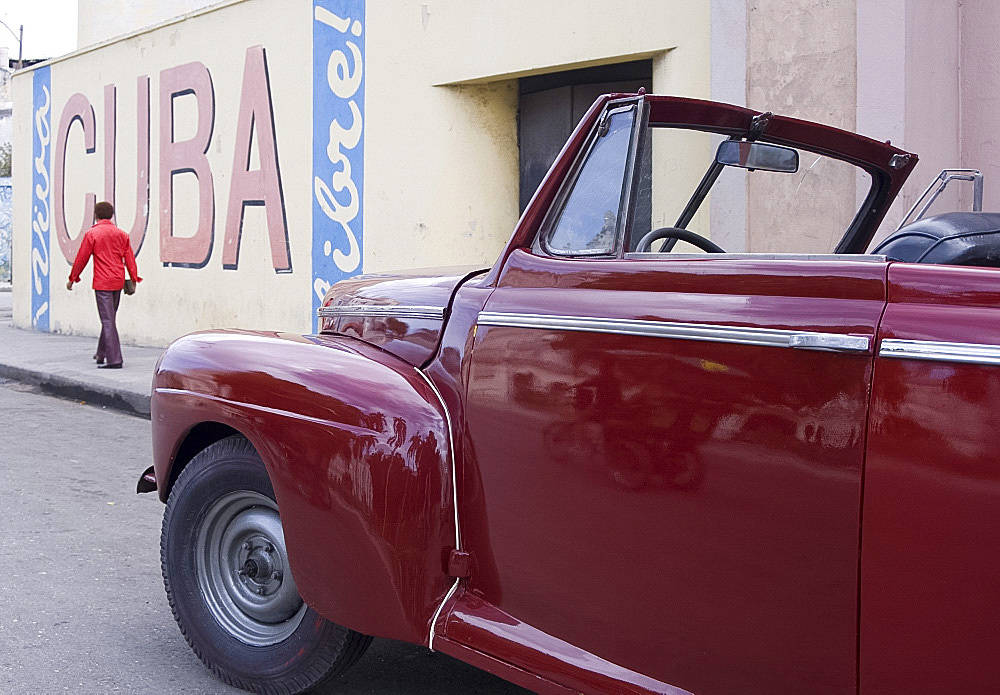 A vintage car near a 'Viva Cuba' sign painted on a wall in cental Havana, Cuba, West Indies, Central America