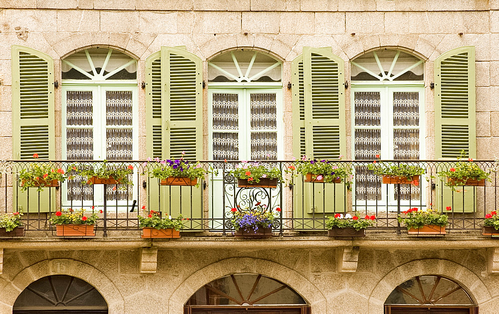 Colourful wooden shutters and a flower covered balcony in Dinan, Brittany, France, Europe