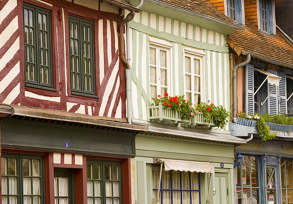 Colourful half timbered houses with geranium filled flower boxes in Beaumont en Auge, Normandy, France, Europe