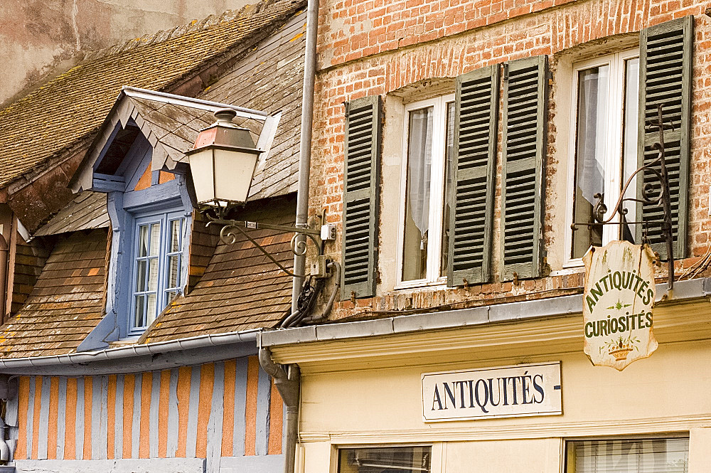 Half timbered house painted pink and blue and signs in Beaumont en Auge, Pays d'Auge, Normandy, France, Europe