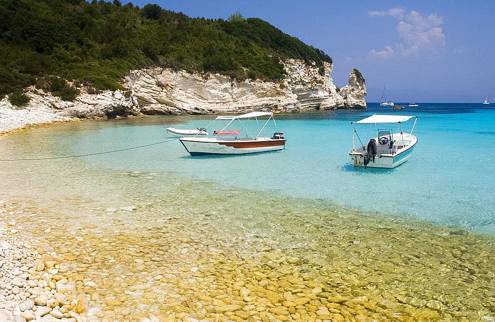 Boats and limestone cliffs at Mesovrika Beach on the northeast coast, Anti-Paxos, Ionian Islands, Greek Islands, Greece, Europe