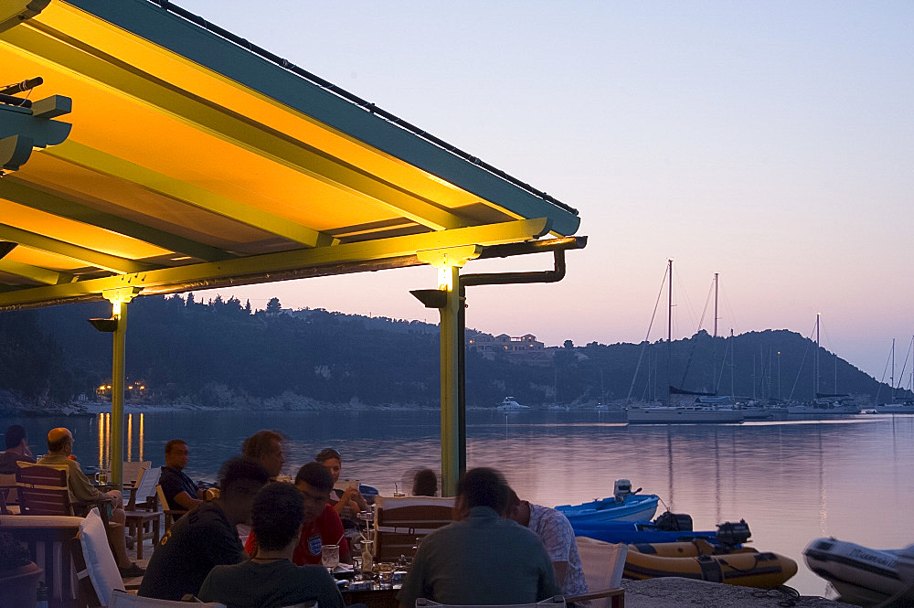 A waterside taverna at dusk in Lakka, Paxos, Ionian Islands, Greek Islands, Greece, Europe