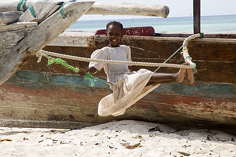 A girl on a makeshift swing on the beach at Nungwi, Zanzibar, Tanzania, East Africa, Africa
